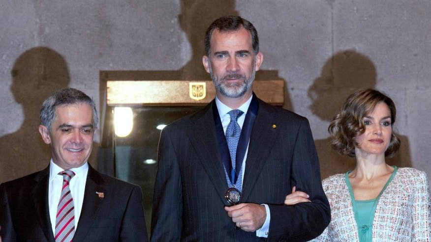Spain's King Felipe VI, center, poses for the press along with Mexico City's Mayor Miguel Angel Mancera, left, and Queen Letizia, right, as they depart City Hall after a meeting in Mexico City, Monday, June 29, 2015. The Spanish royals are in Mexico for an official four-day visit. (AP Photo/Marco Ugarte)