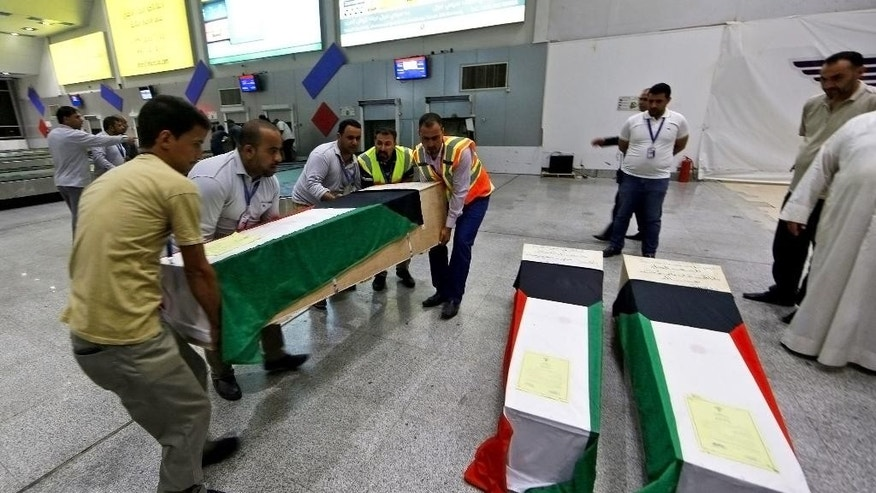 In this Saturday, June 27, 2015 photo, men arrange coffins draped with Kuwaiti flags belonging to a victim of a suicide bombing that targeted a Shiite mosque in Kuwait on Friday, as they arrive to Najaf Airport, for the funeral procession, in the Shiite holy city of Najaf, Iraq. Kuwaiti authorities on Sunday identified the suicide bomber behind an attack on a Shiite mosque that killed more than two dozens as a Saudi citizen who flew into the Gulf nation just hours before he blew himself up. (AP Photo/ Jaber al-Helo)