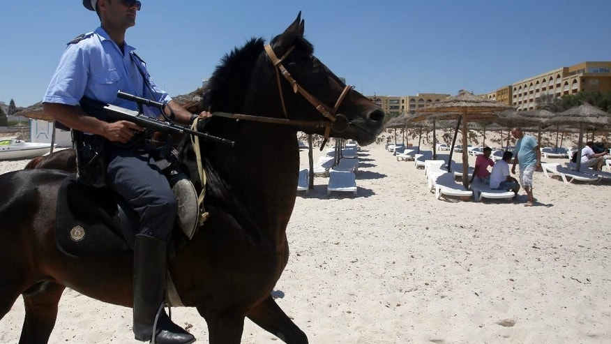 A Tunisian police officer on horse patrol the beach in front of the Imperial Marhaba Hotel in Sousse, Tunisia, Sunday, June 28, 2015. Tunisia's top security official says 1,000 extra police are being deployed at tourist sites and beaches in the North African nation. (AP Photo/Darko Vojinovic)