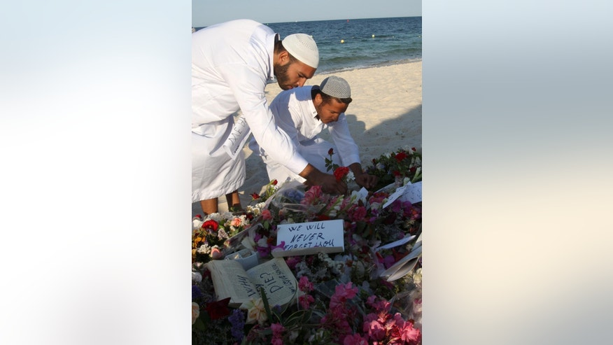Residents of the coastal town of Sousse in Tunisia place flowers and messages during a gathering at the scene of Friday's shooting attack, Sunday, June 28, 2015. The Friday attack on tourists at a beach is expected to be a huge blow to Tunisia's tourism sector, which made up nearly 15 percent of the country's gross domestic product in 2014. (AP Photo/Abdeljalil Bounhar)