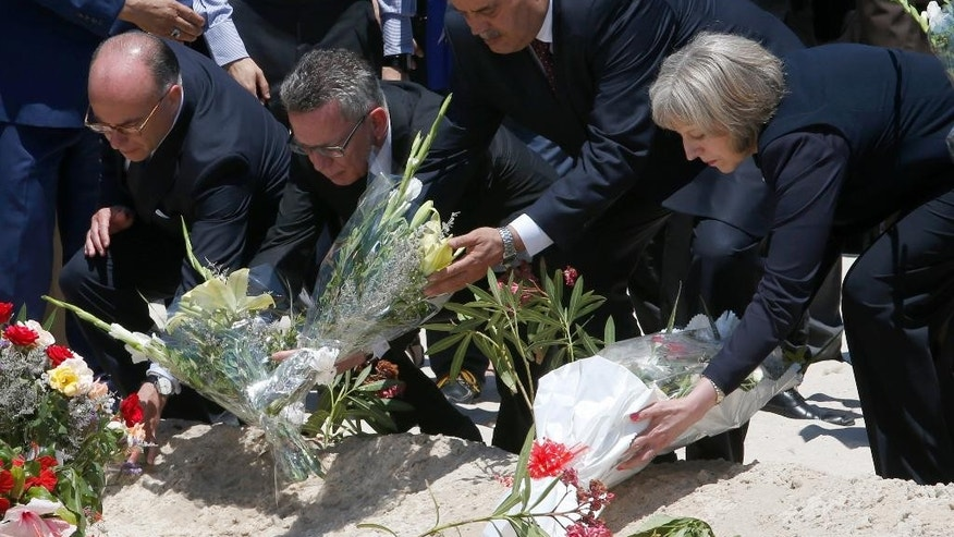 From right to left British Home Secretary Theresa May, Tunisian Interior Minister Mohamed Najem Gharsalli, , German Interior Minister Thomas de Maiziere and French Interior Minister Bernard Cazeneuve  lay flowers on the beach in front of the Imperial Marhaba hotel in the Mediterranean resort of Sousse for the tribute in Sousse, Tunisa, Monday, June 29, 2015. The top security officials of Britain, France, Germany and Belgium are paid homage to the  people killed in the terrorist attack in Sousse on Friday.  (AP Photo/Abdeljalil Bounhar)