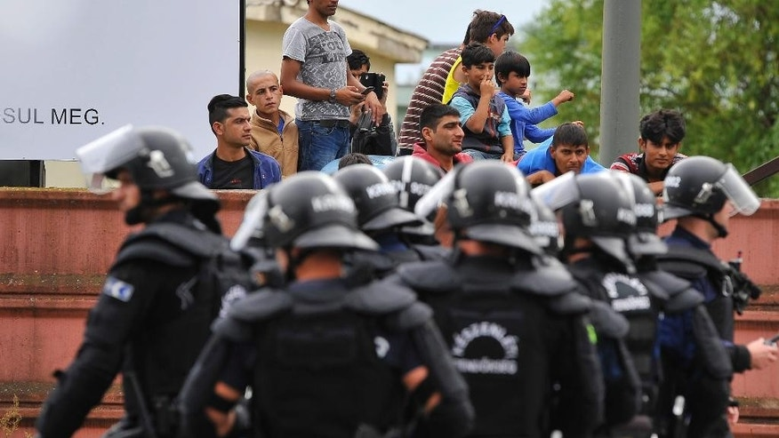 Policemen stand at the entrance of the Debrecen refugee camp in Debrecen, 230 kms from Budapest, Hungary, Monday, June 29, 2015. Police say they used tear gas to stop hundreds of refugees involved in a fight at a refugee camp in this eastern Hungarian city. (Zsolt Czegledi/MTI via AP)