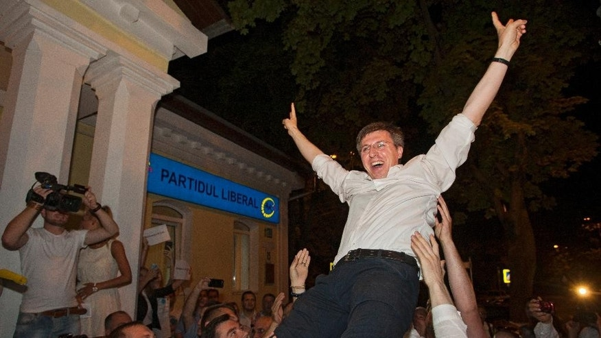 Dorin Chirtoaca, the pro-European candidate for mayor of the Moldovan capital celebrates after seeing exit polls in a runoff for local elections in Chisinau, Moldova, Sunday, June 28, 2015. Near-final results gave a pro-European Union candidate a comfortable lead in the runoff vote for mayor of Moldova's capital, in an election seen as a test of whether the former Soviet republic moves closer to the EU or to neighboring Russia. (AP Photo/Dan Morar)