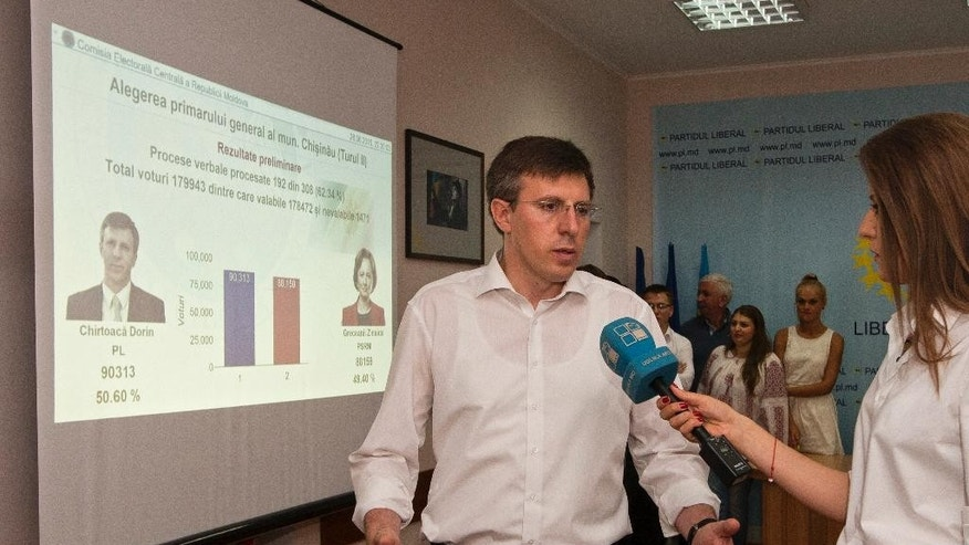 Dorin Chirtoaca, the pro-European candidate for mayor of the Moldovan capital speaks to media after seeing exit polls in a runoff for local elections in Chisinau, Moldova, Sunday, June 28, 2015. Near-final results gave a pro-European Union candidate a comfortable lead in the runoff vote for mayor of Moldova's capital, in an election seen as a test of whether the former Soviet republic moves closer to the EU or to neighboring Russia. (AP Photo/Dan Morar)