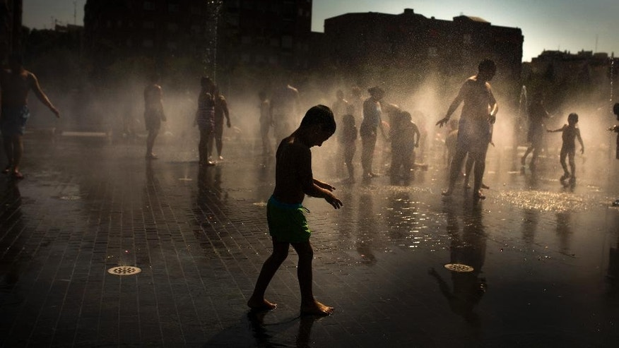 Children play as they cool down in a fountain beside Manzanares river in Madrid,  Spain, Sunday, June 28, 2015. Weather stations across Spain are warning people to take extra precautions as a heat wave engulfs much of the country, increasing the risk of wildfires. The country's meteorological agency says a mass of hot air originating in Africa is moving northwards, bringing with it until at least Monday temperatures reaching 40 C (104 F). (AP Photo/Andres Kudacki)