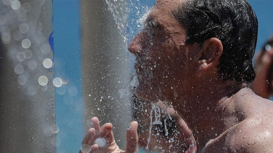 A man cools off at a beach in Barcelona, Spain, Sunday, June 28, 2015. Weather stations across Spain are warning people to take extra precautions as a heat wave engulfs much of the country, increasing the risk of wildfires. The country's meteorological agency says a mass of hot air originating in Africa is moving northwards, bringing with it until at least Monday temperatures reaching 40 degrees centigrade (104 Fahrenheit). (AP Photo/Manu Fernandez)
