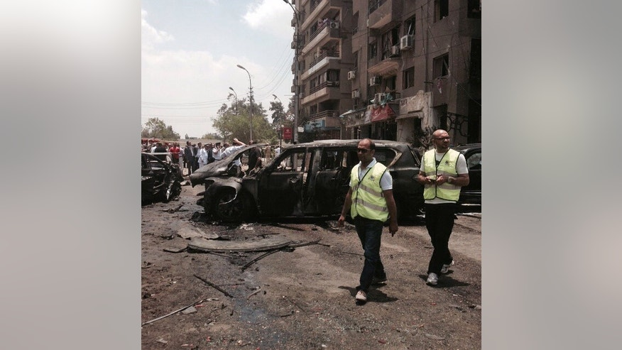 Emergency personnel inspect damage after a bomb attack has targeted Egypt's prosecutor general in the Heliopolis district of Cairo, Egypt, Monday, June 29, 2015. The official says Monday's attack targeted Hisham Barakat's convoy. The prosecutor's two security guards and a civilian were wounded. The official says it's not yet clear if Barakat was hurt or not. (AP Photo/Ahmed Hatem)