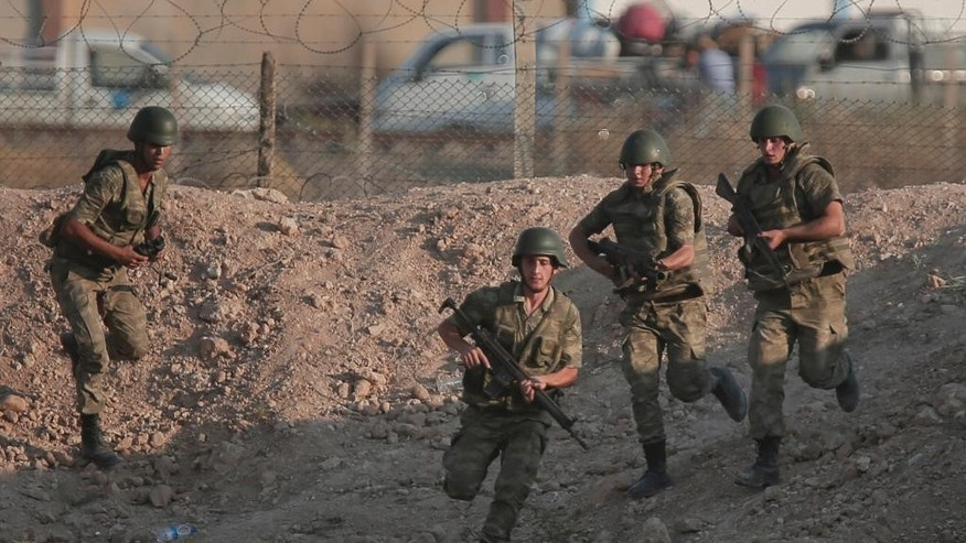 FILE-In this Monday, June 15, 2015 file photo taken from the Turkish side of the border between Turkey and Syria, Turkish soldiers run to their new positions next to the border fence in Akcakale, southeastern Turkey. As Kurdish rebels in northern Syrian rack up wins against the Islamic State group, Turkey's press is once again abuzz with talk of plans for a long-debated intervention aimed at pushing the radical religious group back from its border, and outflanking any Kurdish attempt at creating a state along Turkey's southern frontier. (AP Photo/Lefteris Pitarakis, file)