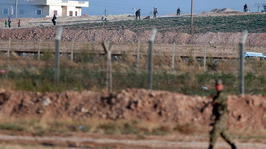FILE-In this Monday, June 15, 2015 file photo taken from the Turkish side of the border between Turkey and Syria, in Akcakale, southeastern Turkey, showing a Turkish soldier walking by the border fence with Syria while in the background, Kurdish fighters, top right, advance, as civilians, top left, flee the outskirts of Tal Abyad, Syria. As Kurdish rebels in northern Syrian rack up wins against the Islamic State group, Turkey's press is once again abuzz with talk of plans for a long-debated intervention aimed at pushing the radical religious group back from its border, and outflanking any Kurdish attempt at creating a state along Turkey's southern frontier. (AP Photo/Lefteris Pitarakis, file)