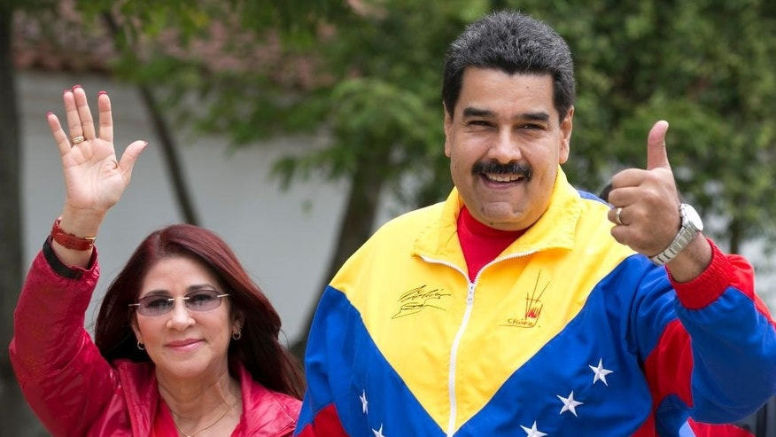 Venezuela's President Nicolas Maduro and first lady, Cilia Flores, left, gesture to supporter as they arrive at a poll station during ruling party primary elections in Caracas, Venezuela, Sunday, June 28, 2015. The PSUV, United Socialist Party of Venezuela held nationwide primaries today to select candidates for the upcoming December legislative elections. (AP Photo/Ariana Cubillos)