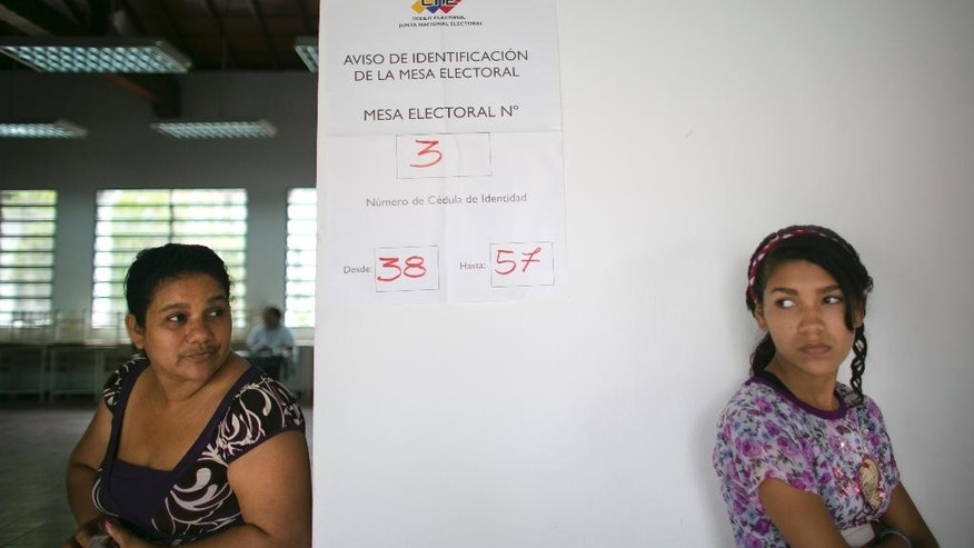 Voters wait to vote at a poll station during ruling party primary elections in Caracas, Venezuela, Sunday, June 28, 2015. The PSUV, United Socialist Party of Venezuela held nationwide primaries today to select candidates for the upcoming December legislative elections. (AP Photo/Ariana Cubillos)