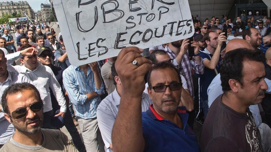 "FILE - This Thursday, June 25, 2015 file photo shows a striking taxi driver holding a placard which read, ""Stop Uber, Stop listening,"" referring to the new US spying report in France, during a taxi drivers demonstration in Paris, France. French authorities took two Uber managers into custody for questioning on Monday over ""illicit activity"" involving its low-cost service. The detentions came amid rising tensions between the government and the ride-hailing company, which culminated last week in a violence-marred taxi strike that blocked roads around the country. (AP Photo/Michel Euler, File)"