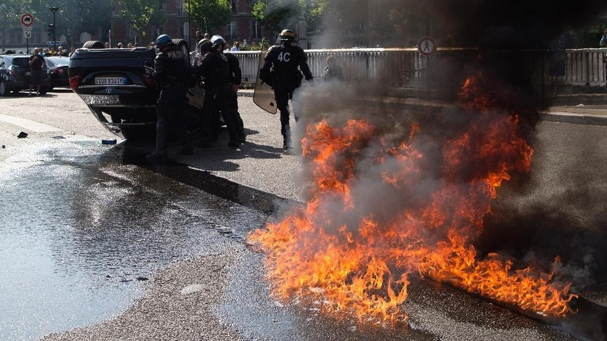 "FILE - This Thursday, June 25, 2015 file photo shows riot police officers standing by an overthrown car during a taxi drivers demonstration in Paris, France. French authorities took two Uber managers into custody for questioning on Monday over ""illicit activity"" involving its low-cost service. The detentions came amid rising tensions between the government and the ride-hailing company, which culminated last week in a violence-marred taxi strike that blocked roads around the country. (AP Photo/Michel Euler, File)"