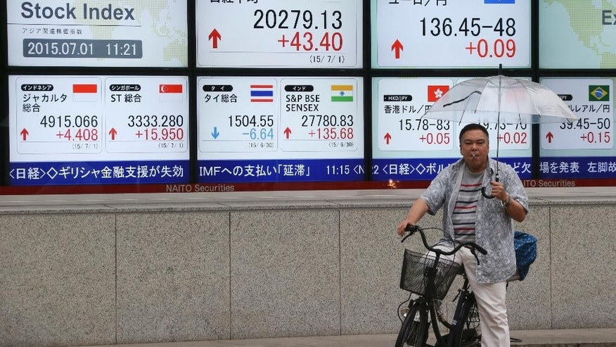 """A man waits in front of an electronic stock board of a securities firm in Tokyo, Wednesday, July 1, 2015. The mood among big Japanese corporations is unexpectedly upbeat despite recent data showing the recovery appears to be stalling. The Bank of Japan's quarterly """"tankan"""" business survey released Wednesday showed a reading of 15 in June, up from 12 in March, for large manufacturers. (AP Photo/Koji Sasahara)"""