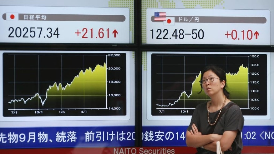 """A woman stands in front of an electronic stock board of a securities firm in Tokyo, Wednesday, July 1, 2015. The mood among big Japanese corporations is unexpectedly upbeat despite recent data showing the recovery appears to be stalling. The Bank of Japan's quarterly """"tankan"""" business survey released Wednesday showed a reading of 15 in June, up from 12 in March, for large manufacturers. (AP Photo/Koji Sasahara)"""