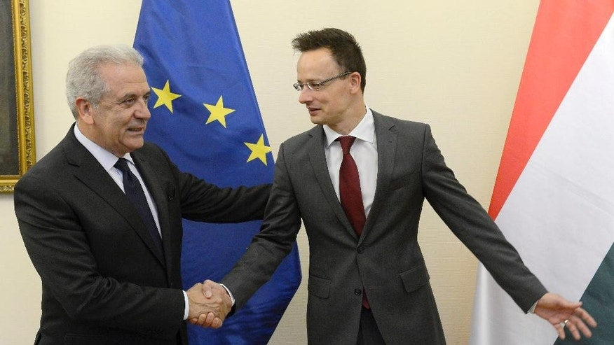 European Commissioner in charge of migration, home affairs and citizenship Dimitris Avramopoulos, left, is guided by Hungarian Minister of Foreign Affairs and Trade Peter Szijjarto during their meeting at the foreign ministry in Budapest, Hungary, Tuesday, June 30, 2015. (Lajos Soos/MTI via AP)