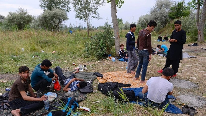 Refugees from Afghanistan gather in no man's land between an old, partly ruined brick factory and a dump on the outskirts of Subotica, northern Serbia, near the Hungarian border, Monday, June 29, 2015. Illegal migrants usually wait here until they can cross the border into Hungary and the Schengen zone of the European Union. (Edvard Molnar/MTI via AP)