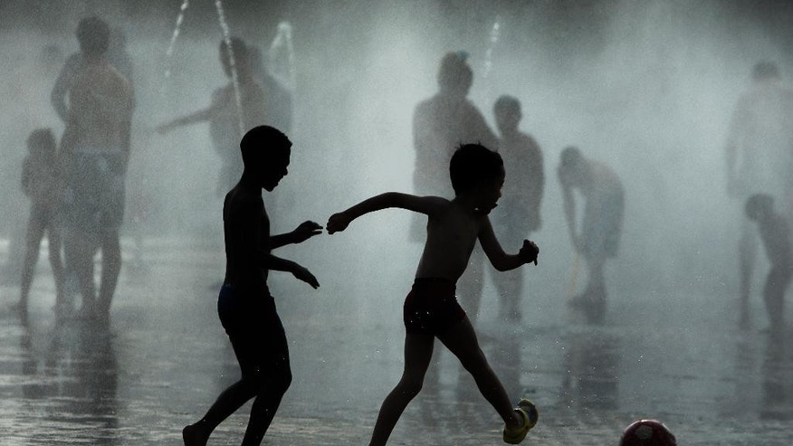 Children play soccer as they cool down in a fountain beside Manzanares river in Madrid, Spain, Monday, June 29, 2015. Weather stations across Spain are warning people to take extra precautions as a heat wave engulfs much of the country, increasing the risk of wildfires. The country's meteorological agency says a mass of hot air originating in Africa is moving northwards, bringing with it until at least Monday temperatures reaching 40 Celsius (104 Fahrenheit). (AP Photo/Andres Kudacki)