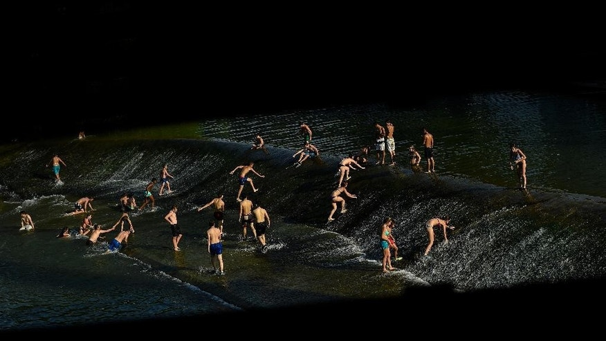 People cool off at a weir in the evening, after a day with temperatures of more than 37 degrees (98 Fahrenheit), at the Arga River which crosses the edge of Pamplona, northern Spain, Monday, June 29, 2015. Weather stations across Spain are warning people to take extra precautions as a heat wave engulfs much of the country, increasing the risk of wildfires. The country's meteorological agency says a mass of hot air originating in Africa is moving northwards, bringing with it until at least Monday temperatures reaching 40 C. (AP Photo/Alvaro Barrientos)