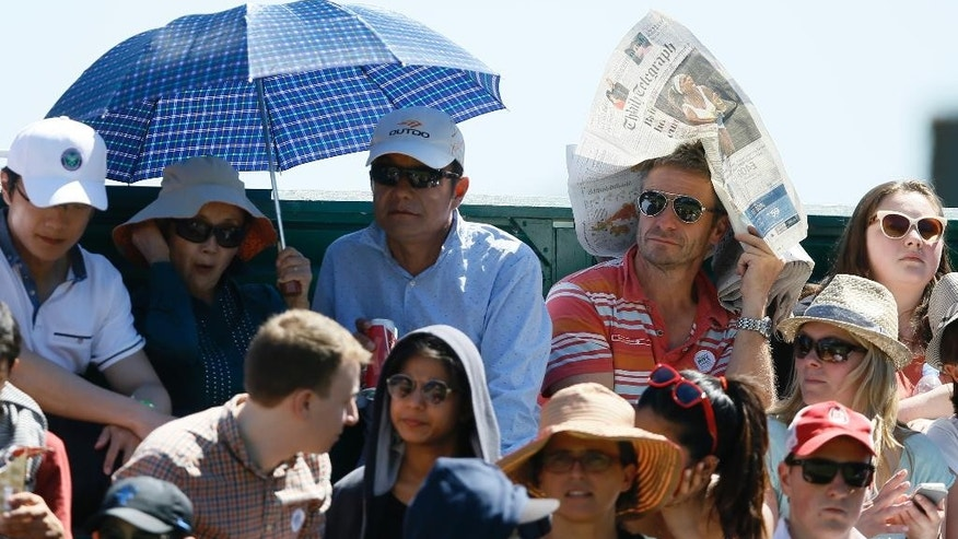 Spectators shelter from the sun and watch the singles first round match between Angelique Kerber of Germany and Carina Witthoeft of Germany at the All England Lawn Tennis Championships in Wimbledon, London, Tuesday June 30, 2015. (AP Photo/Kirsty Wigglesworth)