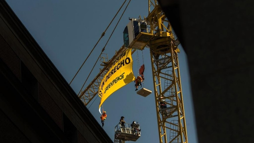 """Firefighters, bottom, arrive as Greenpeace activists, top left and right, display a banner reading """"Protest is a right"""" as they hug from a crane to protest against the Public Security Law above the Parliament in Madrid, Spain, Tuesday, June 30, 2015. Greenpeace activists have hung a banner defending people's right to protest from a construction crane close to Spain's Parliament as part of activities to highlight the coming into effect of the Public Security Law, known as the """"gag law,"""" on July 1. (AP Photo/Andres Kudacki)"""