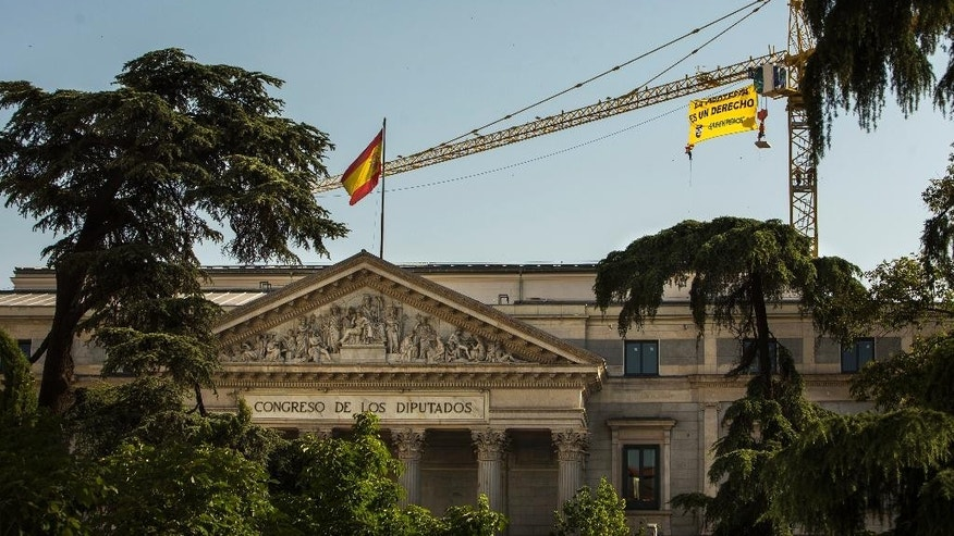 "Greenpeace activists display a banner reading ""Protest is a right"" as they hung from a crane to protest against the Public Security Law above the Parliament in Madrid, Spain, Tuesday, June 30, 2015. Greenpeace activists have hung a banner defending people's right to protest from a construction crane close to Spain's Parliament as part of activities to highlight the coming into effect of the Public Security Law, known as the ""gag law,"" July 1. (AP Photo/Andres Kudacki)"