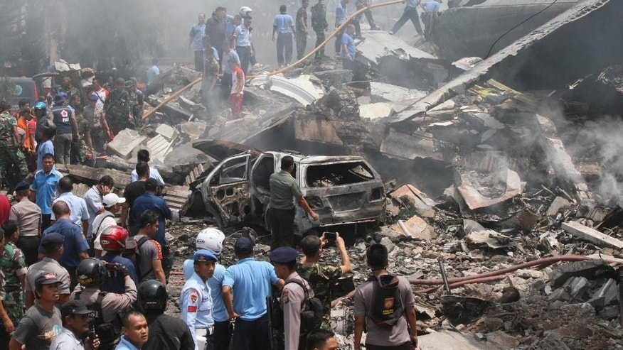 Firefighters and military personnel inspect the site where an Air Force cargo plane crashed in Medan, North Sumatra, Indonesia, tuesday, June 30, 2015. An Indonesian Air Force Hercules C-130 plane with 12 crew aboard has crashed into a residential neighborhood in the country's third-largest city Medan. (AP Photo/Gilbert Manullang)