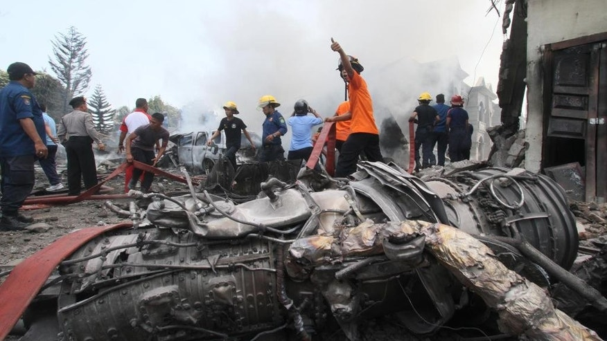 Firefighters and military personnel work at the site where an Air Force cargo plane crashed in Medan, North Sumatra, Indonesia, Tuesday, June 30, 2015. An Indonesian Air Force Hercules C-130 plane with 12 crew aboard has crashed into a residential neighborhood in the country's third-largest city Medan. (AP Photo/Gilbert Manullang)
