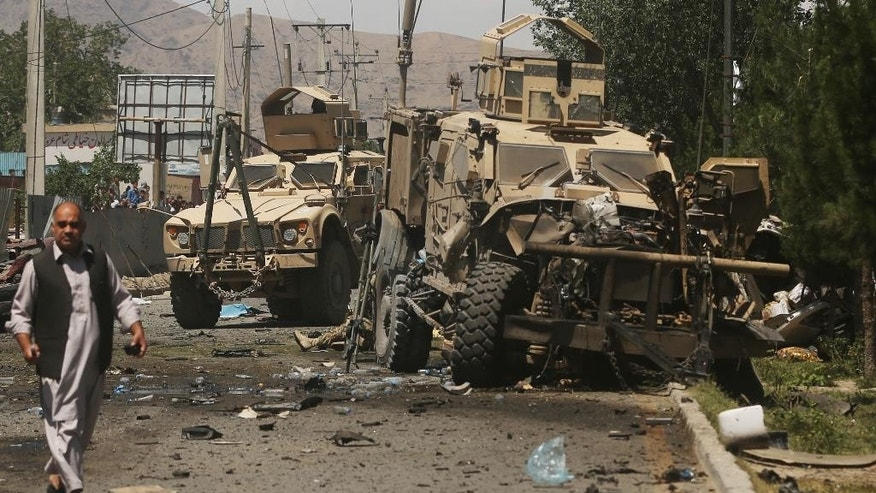 A destroyed armored vehicle remains at the site of a blast targeting the NATO convoy in Kabul, Afghanistan, Tuesday, June 30, 2015. It comes a week after an audacious attack on the nation's parliament, which highlighted the ability of insurgents, who have been fighting to overthrow the Kabul government for almost 14 years, to enter the highly fortified capital to stage deadly attacks. (AP Photo/Massoud Hossasini)