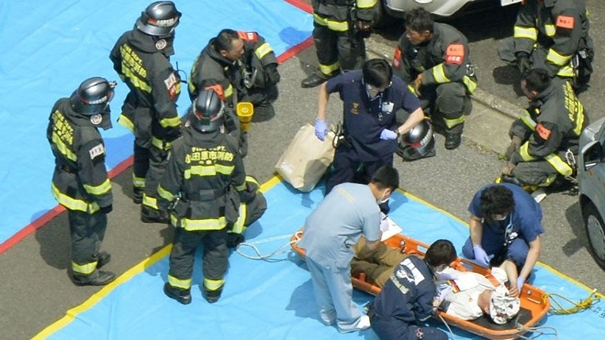 June 30, 2015: Passengers of a Shinkansen bullet train which made an emergency stop, receive treatment in Odawara, west of Tokyo.