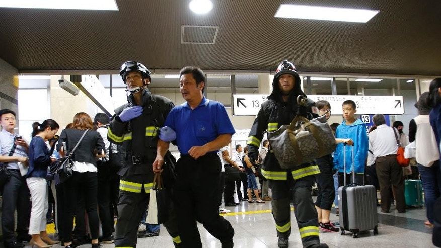 A passenger is escorted by firefighters after getting off a high-speed bullet train where a man set himself of fire, at Odawara station in Odawara, west of Tokyo, Tuesday, June 30, 2015. The man riding one of Japan's high-speed bullet trains set himself on fire Tuesday, killing himself as the coach filled with smoke, Japanese officials and media reports said. (AP Photo/Shizuo Kambayashi)