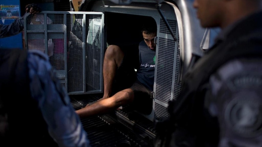 "A man detained as a suspected drug trafficker is placed in a paddy wagon during a police operation at the Mare slum complex in Rio de Janeiro, Brazil, Tuesday, June 30, 2015.  The last soldiers and marines occupying the Mare complex of slums will be replaced by police as part of the program to ""pacify"" and reduce violence in the favela. The process started in April with a June 30 deadline for the army to vacate the neighborhood. (AP Photo/Felipe Dana)"