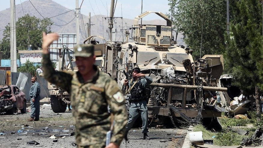 Afghanistan security personnel work at at the site of a suicide attack on a NATO convoy in Kabul, Afghanistan, Tuesday, June 30, 2015. It comes a week after an audacious attack on the nation's parliament, which highlighted the ability of insurgents, who have been fighting to overthrow the Kabul government for almost 14 years, to enter the highly fortified capital to stage deadly attacks. (AP Photo/Rahmat Gul)