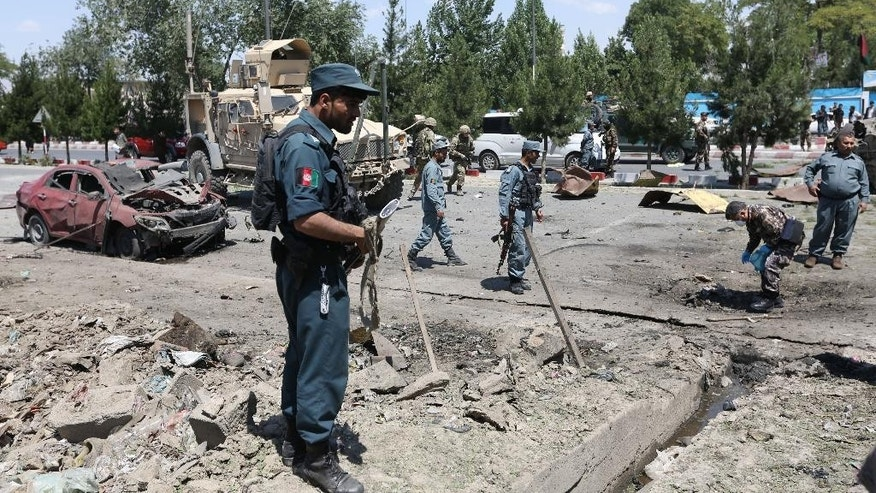 Afghan security personnel investigate site of a suicide attack on a NATO military convoy in Kabul, Afghanistan, Tuesday, June 30, 2015. It comes a week after an audacious attack on the nation's parliament, which highlighted the ability of insurgents, who have been fighting to overthrow the Kabul government for almost 14 years, to enter the highly fortified capital to stage deadly attacks. (AP Photo/Rahmat Gul)
