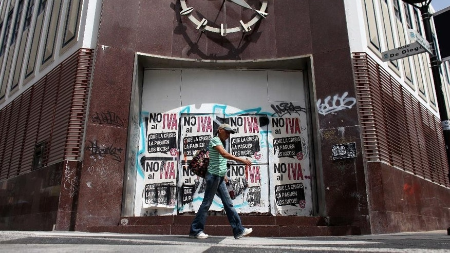 """A woman walks in front of a closed down bank in the neighborhood of Rio Piedras in San Juan, Puerto Rico, Monday, June 29, 2015. The bills on the closed bank doors read in Spanish """"No to the value added tax. Let the rich pay for the crisis."""" International economists released a critical report on Puerto Rico's economy Monday on the heels of the governor's warning that the island can't pay its $72 billion public debt. (AP Photo/Ricardo Arduengo)"""