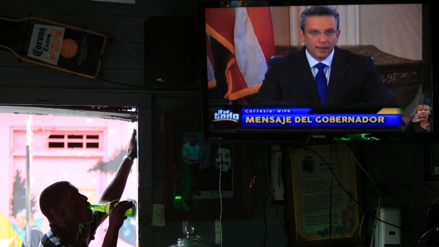 A man drinks a beer in a local bar as he watches Puerto Rico's governor Alejandro Garcia Padilla on television delivering an address on the state of the island's finances, in San Juan, Puerto Rico, Monday, June 29, 2015. The governor said that he will form a financial team to negotiate with bondholders on delaying debt payments and then restructuring $72 billion in public debt that he says the island can't repay. (AP Photo/Ricardo Arduengo)