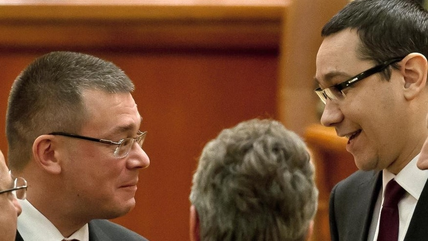 FILE - In this Feb. 9, 2012 file photo  Romanian Premier designate Mihai Razvan Ungureanu, left, speaks to opposition leader Victor Ponta, right, in Bucharest, Romania. Romania's Parliament has approved Tuesday, June 30, 2015,  Ungureanu as the country's spy chief, a position he previously held, which is seen as a defeat for the prime minister Victor Ponta. (AP Photo/Vadim Ghirda, File)