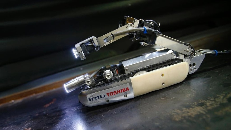 "CORRECTS TO LOCATION - A robot developed by Toshiba Corp. is demonstrated at its laboratory in Yokohama, near Tokyo, Tuesday, June 30, 2015. As Japan struggles in the early stages of decades-long cleanup of the Fukushima nuclear crisis, Toshiba has developed the robot that raises its tail like a scorpion and collects data, and hopefully locate some of melted debris. The ""scorpion"" robot, which is 54 centimeters (21 inches) long when extended, has two cameras, LED lighting and a dosimeter, will be sent into the Unit 2 reactor in August to look. (AP Photo/Shizuo Kambayashi)"