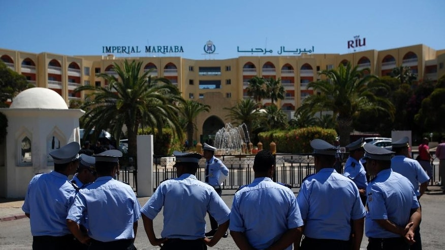 Tunisian police officers guard  Imperial Marhaba hotel during visit of top security officials of Britain, France, Germany and Belgium in Sousse, Tunisia, Monday, June 29, 2015. British Home Secretary Theresa May, French Interior Minister Bernard Cazeneuve, German Interior Minister Thomas de Maiziere and Belgian Interior Minister Jan Jambon joined their Tunisian counterpart on the beach in front of the Imperial Marhaba hotel in the Mediterranean resort of Sousse for the tribute Monday. (AP Photo/Darko Vojinovic)