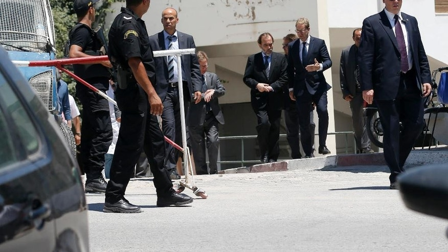 Tunisia's health minister Said Aidi, center left, and British Minister for North Africa Tobias Ellwood, center right, leave from morgue with bodies of several tourists in a local hospital in Tunis, Tunisia, Tuesday, June 30, 2015. Thirty-eight tourists died in a gun attack just days before Tunisia planned to implement heightened security measures for the Muslim fasting month of Ramadan, but those plans had not anticipated an assault on tourist beaches, the country's president said Tuesday. (AP Photo/Darko Vojinovic)