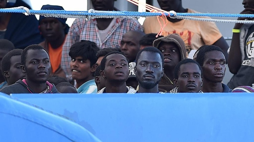 Migrants wait to disembark from the Swedish Coast Guard ship KBV 001 Poseidon at Messina harbor, Italy, Tuesday, June 30, 2015. (AP Photo/Carmelo Imbesi)
