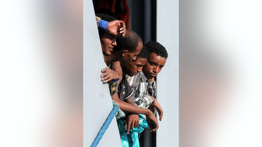 Migrants wait to disembark from the Irish naval ship Le Eithne, at the Palermo harbor, Italy, Tuesday, June 30, 2015. (AP Photo/Alessandro Fucarini)