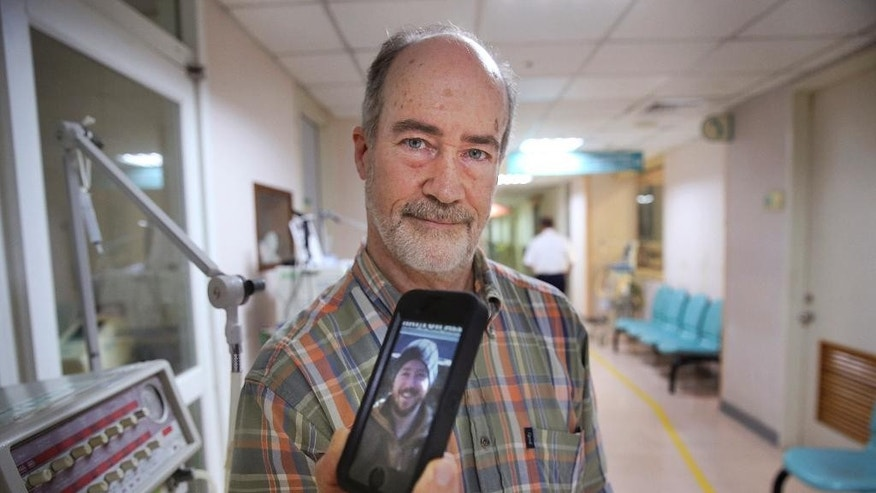 CORRECTS SPELLING OF HAAS' HOMETOWN FROM MOUNT VERNON TO MONT VERNON - Standing outside of the intensive care unit at a local hospital, Roger Haas, of Mont Vernon, New Hampshire, holds an iPhone photo of his son Alex Haas, 26, seriously burned in Saturday's accidental water park fire in Taipei, Taiwan, Wednesday, July 1, 2015. Investigators in Taiwan were focusing Monday on the possibility that a cigarette butt or spark caused the blaze that burned 498 people, killing one, at a weekend water park party when colored powder sprayed from the stage caught fire. More than 400 people remained hospitalized, including 202 in serious condition, city officials said. (AP Photo/Wally Santana)