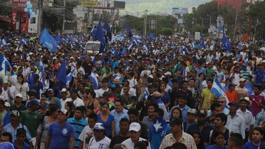 Thousands march in support of President Juan Orlando Hernández in the capital city of Tegucigalpa, Honduras, Sunday, June 28, 2015. President Hernández has been under pressure over a corruption scandal that involved the alleged embezzlement of as much as $120 million from the Central American country's Social Security Institute. Another scandal involves selling overpriced or defective medicines to the government. (AP Photo/Fernando Antonio)