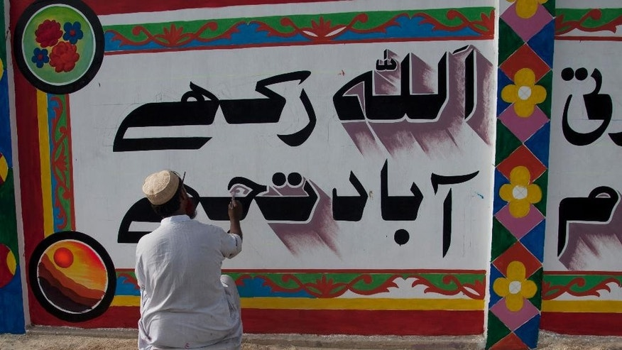 """In this photo taken Thursday, June 4, 2015, a Pakistani calligraphist paints, """"God bless you,"""" in Urdu over violent graffiti on the wall of an apartment complex and offices after getting permission in Karachi, Pakistan. Activists and artists in Pakistan hope to combat extremism through art, by painting murals over violent graffitti and distributing a comic book in schools aimed at turning young people away from violence. (AP Photo/Shakil Adil)"""