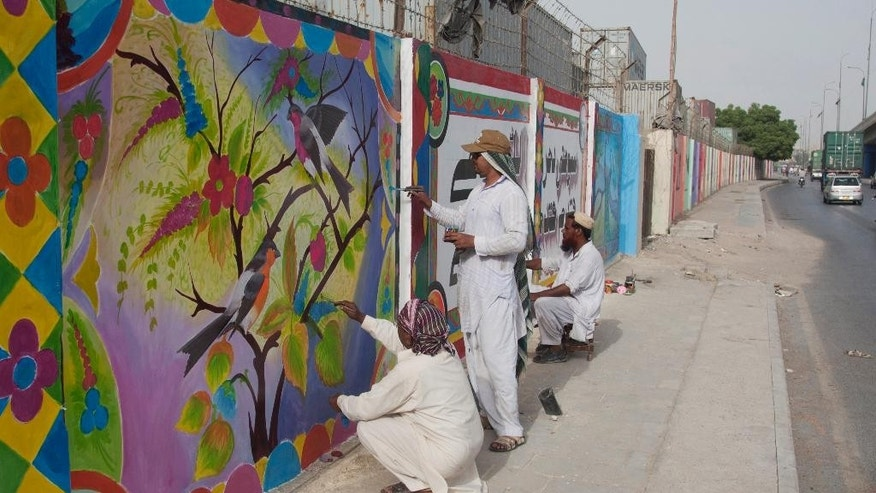In this photo taken Thursday, June 4, 2015, Pakistani local artists paint over violent graffiti on the wall of an apartment complex and offices after getting permission in Karachi, Pakistan. Activists and artists in Pakistan hope to combat extremism through art, by painting murals over violent graffiti and distributing a comic book in schools aimed at turning young people away from violence. (AP Photo/Shakil Adil)