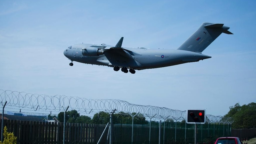 A plane repatriating some of the British victims of the Tunisia beach attack comes in to land at the RAF (Royal Air Force) Brize Norton base in Brize Norton, England, Wednesday, July 1, 2015.  Britain on Wednesday began repatriating the remains of victims of last week's terror attack at a Tunisian beach resort.  (AP Photo/Matt Dunham)