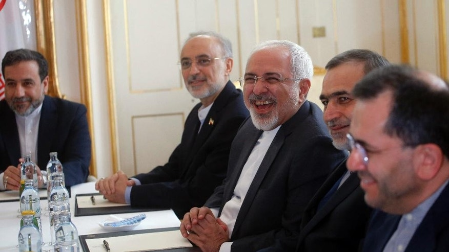 Iranian Foreign Minister Javad Zarif, center,laughs during a meeting with U.S. Secretary of State John Kerry at a hotel in Vienna, Austria, Tuesday June 30, 2015. Pushing past a deadline, world powers and Iran extended negotiations for a comprehensive nuclear agreement by a week on Tuesday as the U.N. nuclear agency prepared to announce Tehran had met a key condition. (Carlos Barria/Pool via AP)