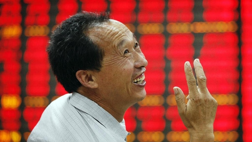 In this June 30, 2015 photo, a stock investor chats at a brokerage house in Huaibei in central China's Anhui province.  Chinese authorities are scrambling to reassure jittery investors after soaring stock markets plunged, threatening to set back economic reform plans. The market benchmark soared 150 percent from the start of the boom late last year in one of the world's fastest runups. It hit a peak June 12 and then reversed course and plunged 28 percent. It rebounded temporarily Tuesday, June 30,  before losing 5.2 percent on Wednesday, July 1.  (Chinatopix Via AP) CHINA OUT