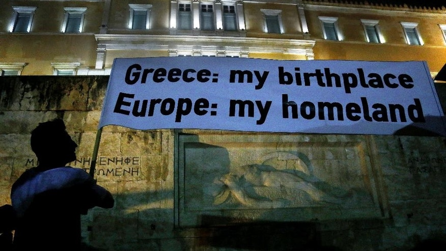 A demonstrator holds a banner during a rally organized by supporters of the YES vote for the upcoming referendum in front of the Greek Parliament in Athens, Tuesday, June 30, 2015. Greece's European creditors were assessing a last-minute proposal Athens made for a new two-year rescue deal, submitted just hours before the country's international bailout program expires and it loses access to billions of euros in funds. (AP Photo/Petros Karadjias)